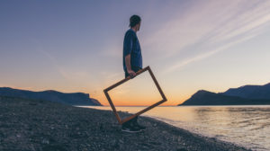 Man holds frame that shows the sunset through his legs.