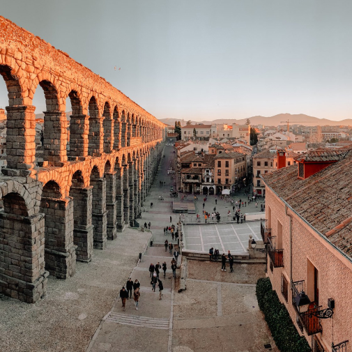 Arched wall and town at sunset.