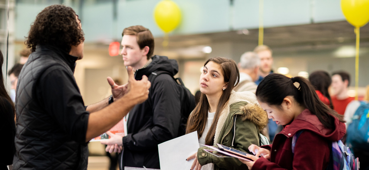 Students speak to Northeastern faculty member at event.