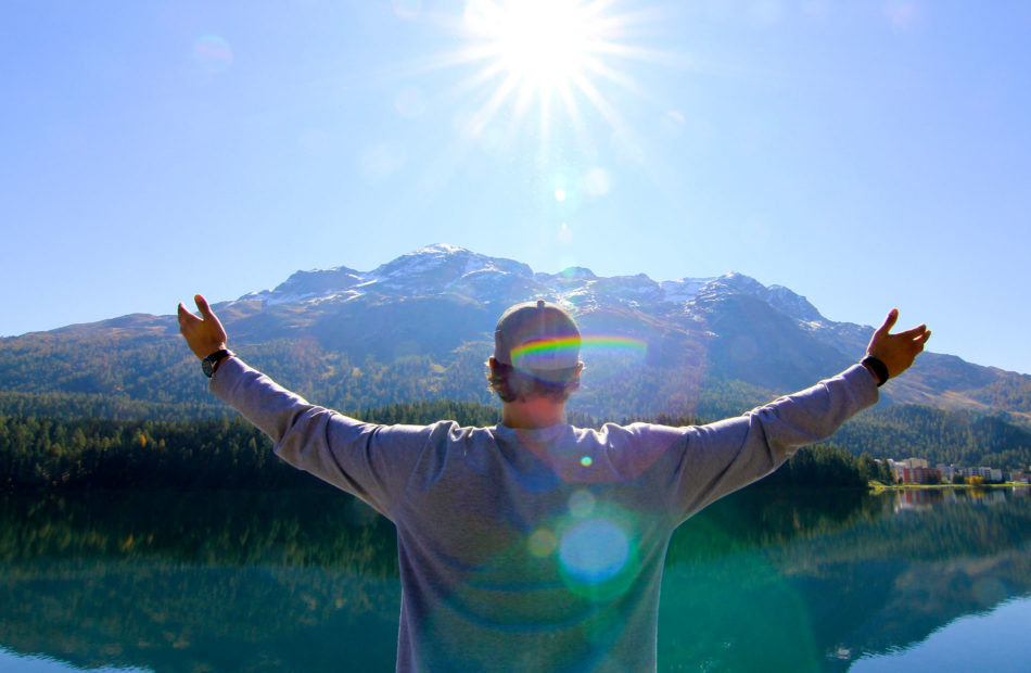 Man holds arms out in front of mountain.