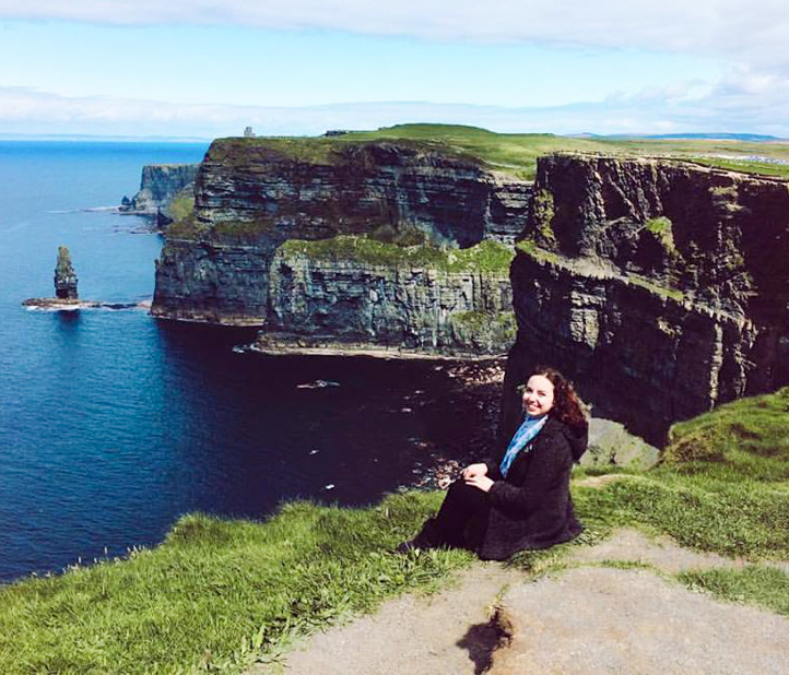 Woman sits beside Cliffs of Moher.
