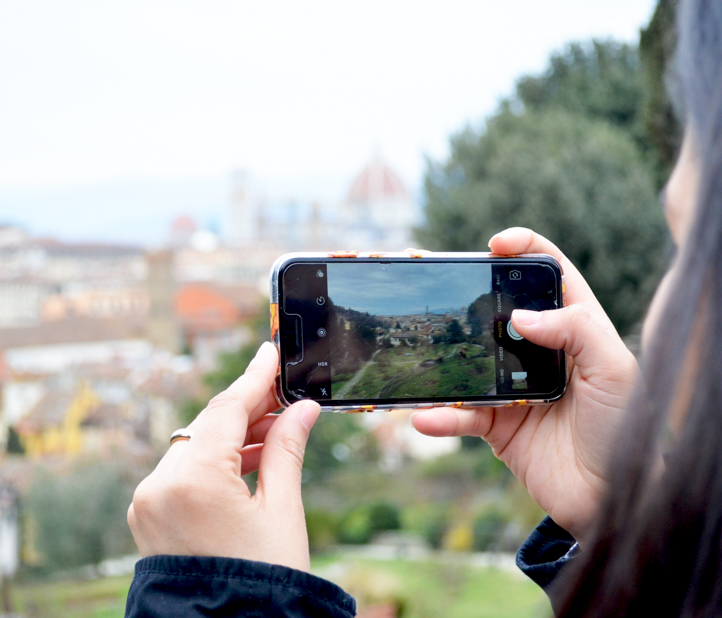 Woman takes photo of gardens on iPhone.