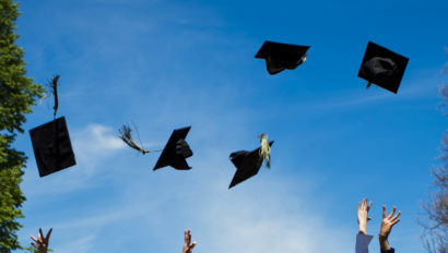 Graduation caps get tossed into the air.