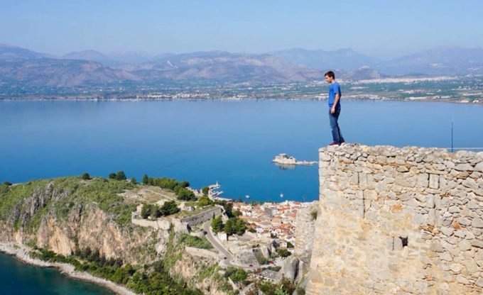 Man stands on wall above peninsula.