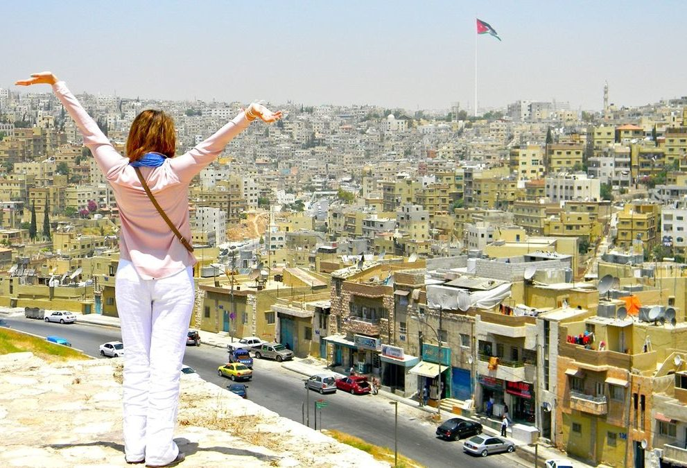 Woman on city overlook holds up arms.