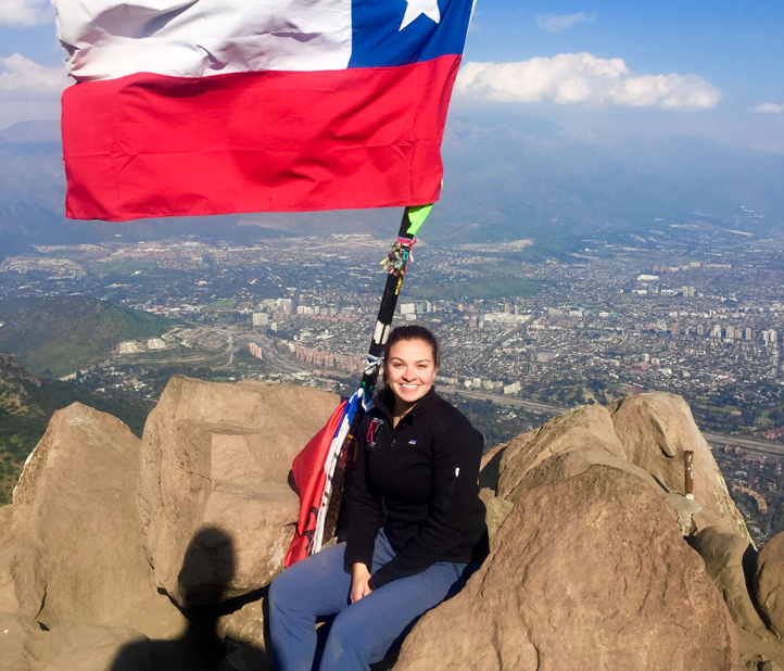 Woman sits on top of mountain with flag.